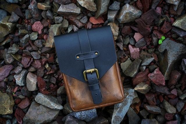 malá kožená taška na kameňoch