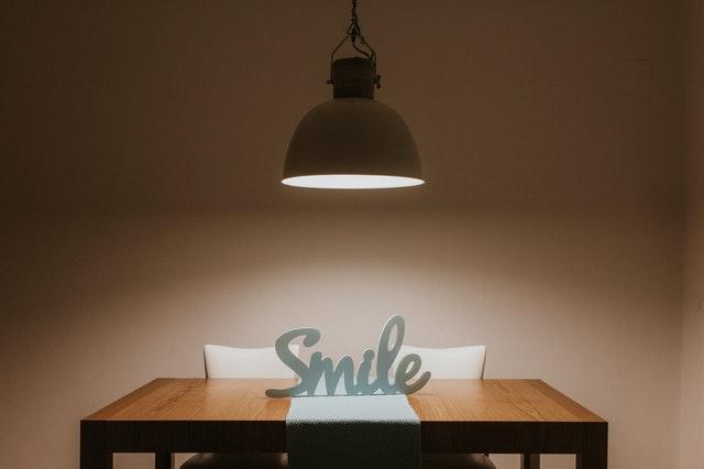 Lampa svieti na drevený stôl s nápisom úsmev.jpg