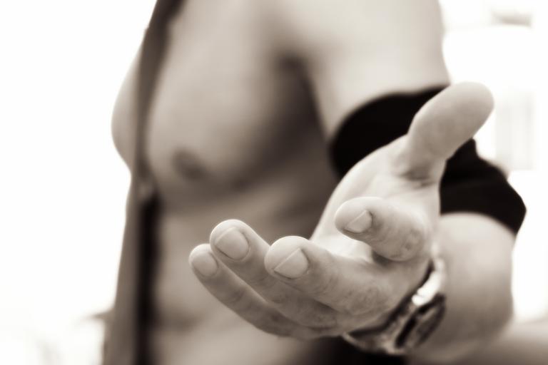 Muž do pol pása podáva ruku,