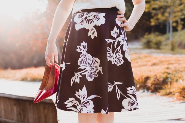 Žena v čiernej sukni s bielymi vzormi drží v rukách topánky.jpg