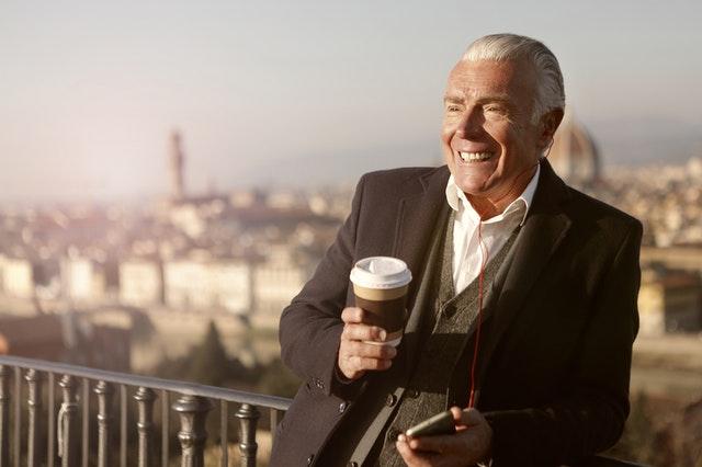 Starší muž v obleku s kávou