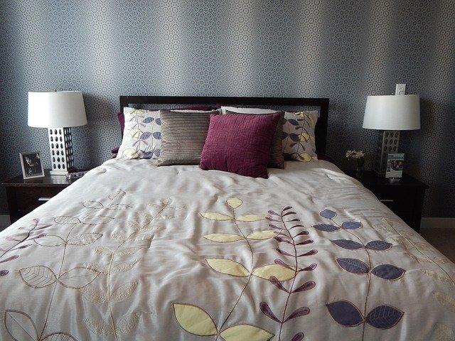 Manželská posteľ s dekou a farebnými vankúšmi